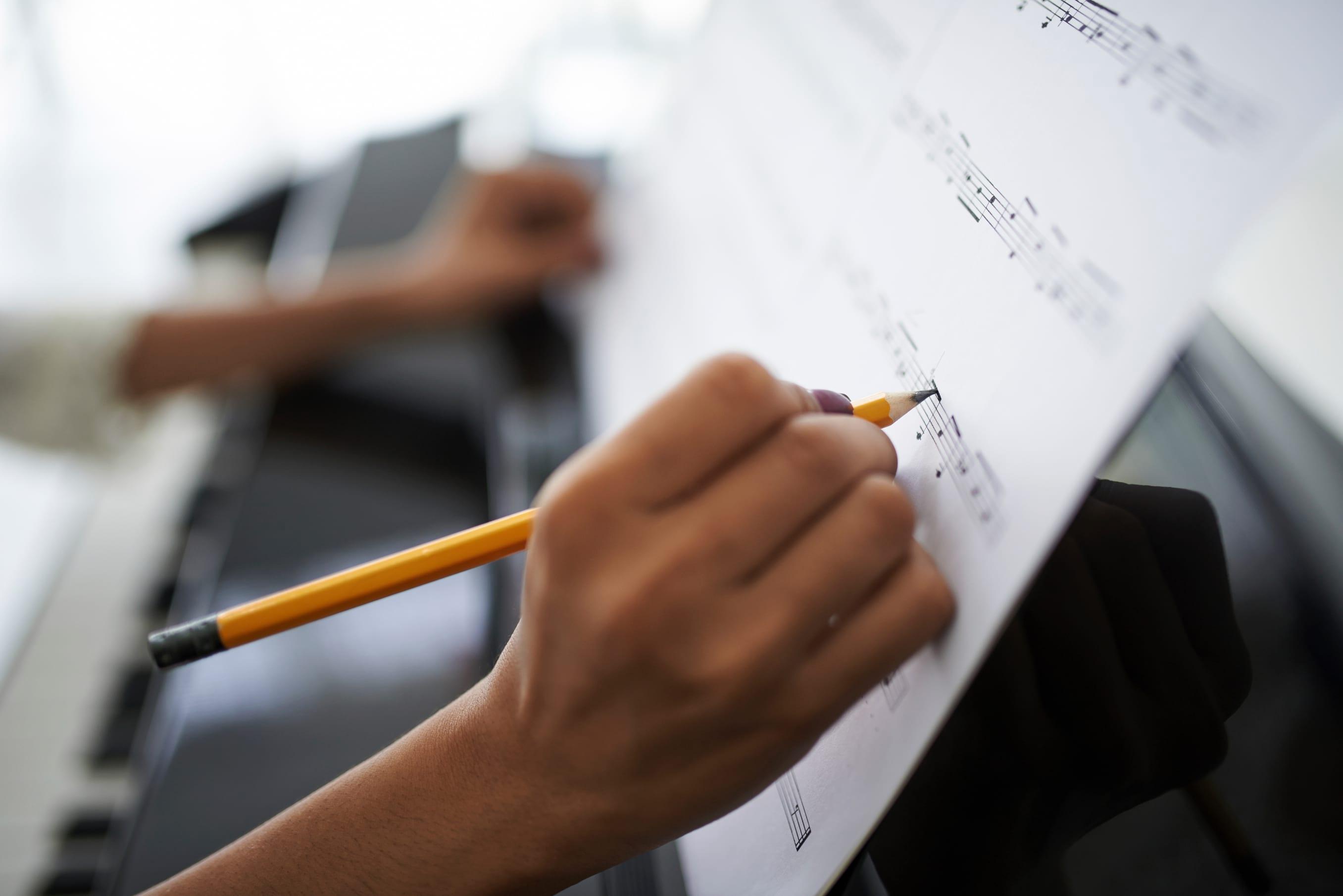 Close-up of female hands correcting music score