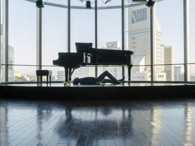 Cesare Picco sdraiato sotto al pianoforte